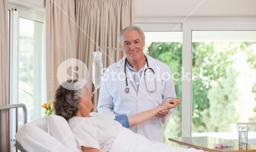 Senior doctor taking the blood pressure of his patient