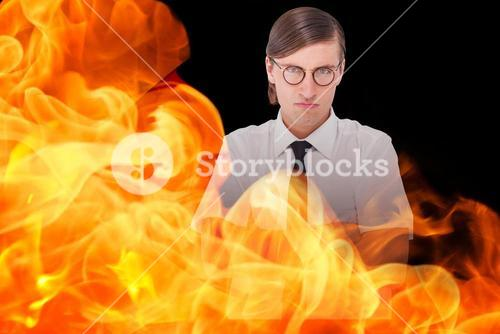 Composite image of geeky businessman looking at camera with arms crossed