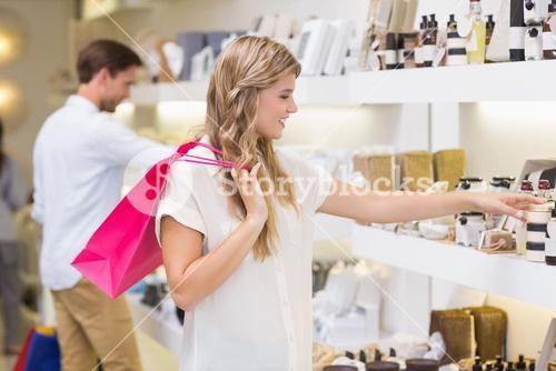 A pretty blonde woman looking at beauty product
