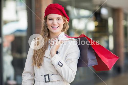 A smiling woman with shopping bags
