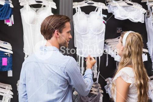 Handsome man showing bodice to his girlfriend