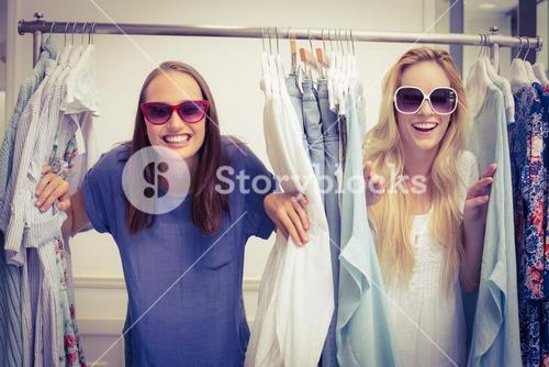 Happy friends looking through the clothes rack