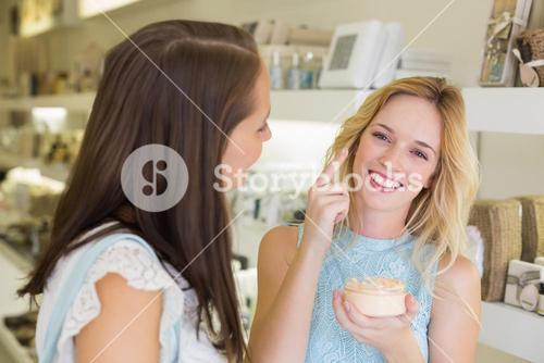 Happy blonde woman applying cosmetic products
