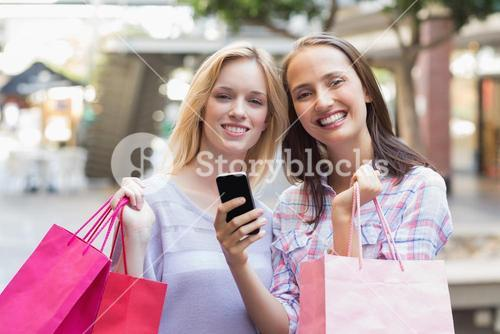 Happy women friends smiling at camera with shopping bags
