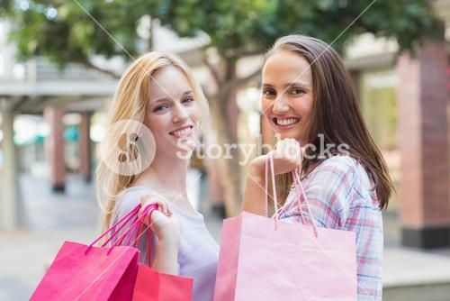 Happy women friends with shopping bags smiling at camera