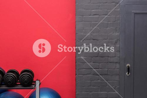 Weights and exercise balls in front of a wall