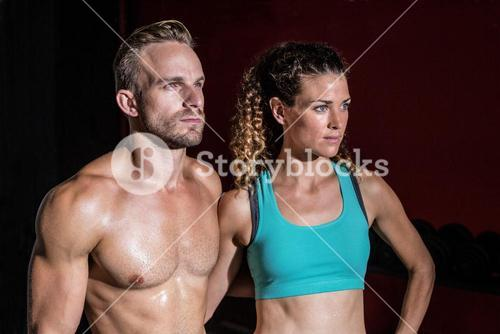 Attentive muscular couple looking away