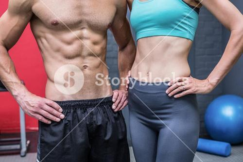 Muscular couple with hands on the hips