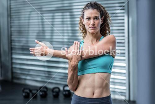 Attentive muscular woman stretching arms