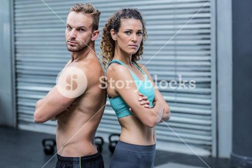 Attentive muscular couple giving back to back