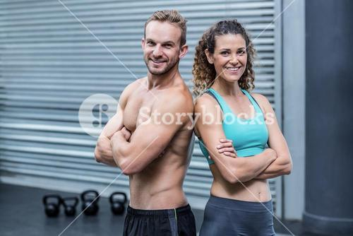 Smiling muscular couple giving back to back