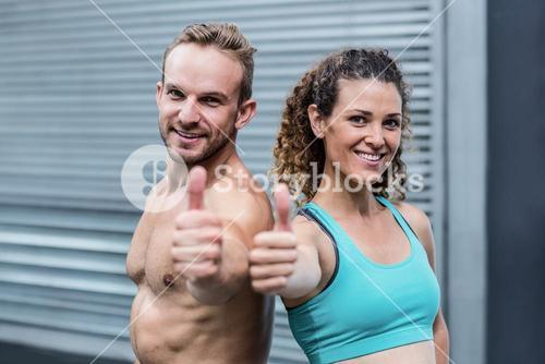 Muscular couple gesturing thumbs up