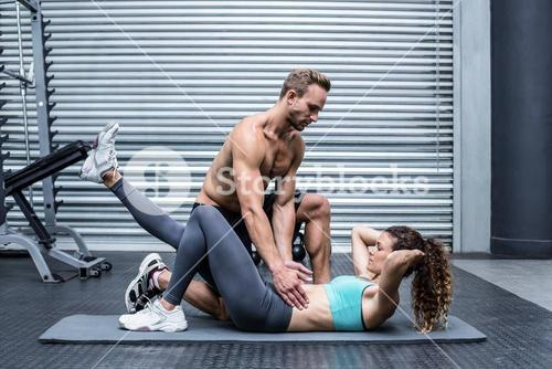 Muscular couple doing abdominal exercises