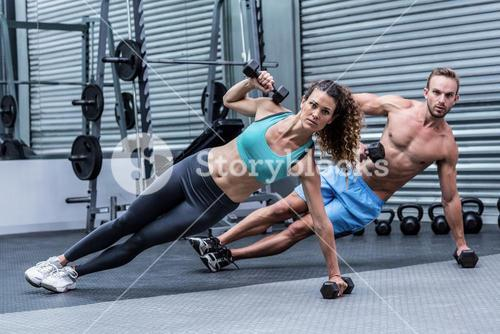 Muscular couple doing side plank