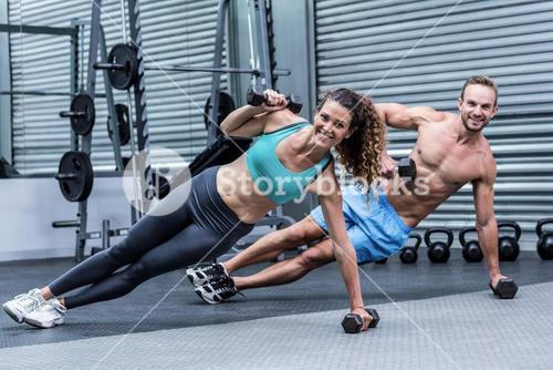Smiling muscular couple doing side plank