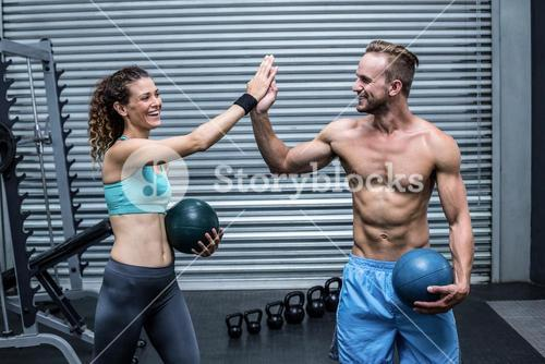 A muscular couple giving high five