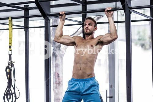 Muscular man doing pull up exercises