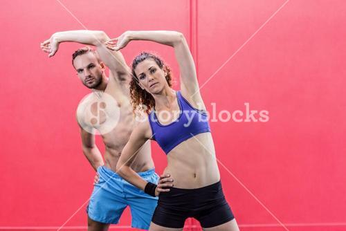 Muscular couple doing arms stretching