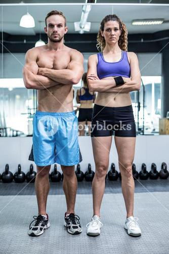 Attentive muscular couple looking at the camera
