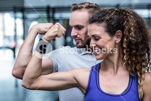 A muscular couple flexing biceps