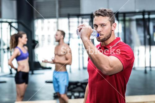 Attentive muscular trainer drinking water