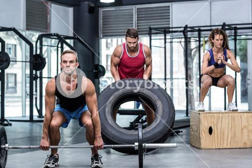 Serious three muscular people lifting and jumping