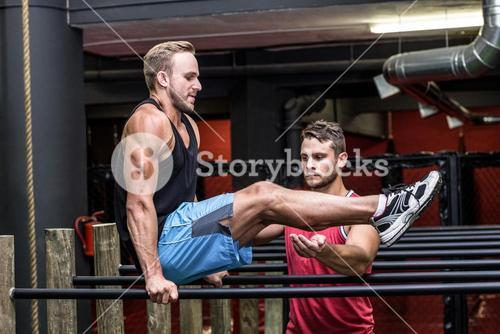 Muscular man doing exercises on parallel bar