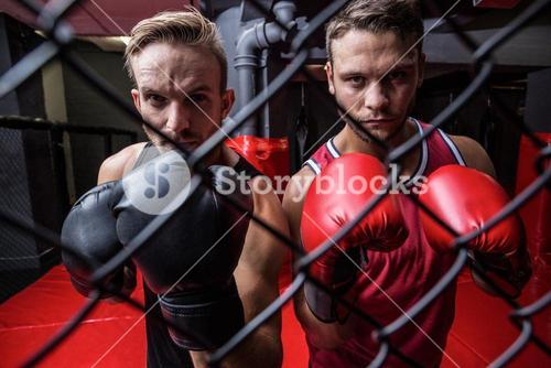 Two boxing men behind the netting