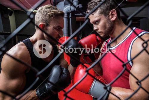 Two determined men boxing behind the netting