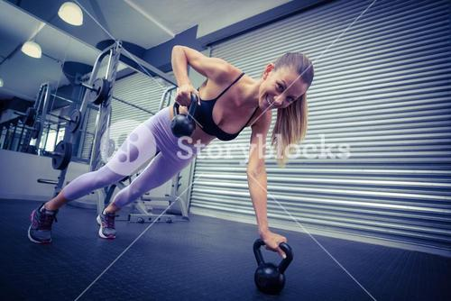 Muscular woman doing pushups with kettlebells