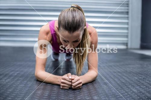 A muscular woman on a plank position