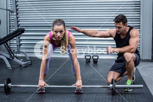 Attentive muscular woman lifting weight