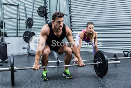 Muscular couple lifting weight together