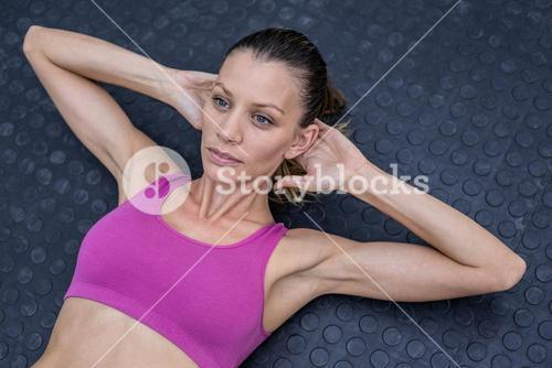 Muscular woman doing abdominal crunch