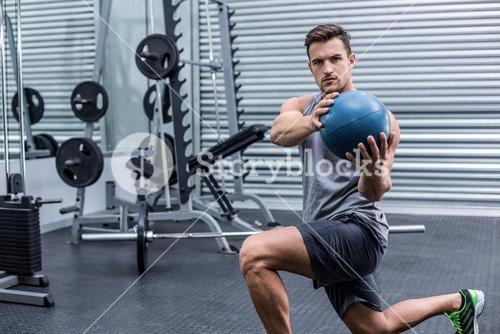 Muscular man doing medecine ball exercises