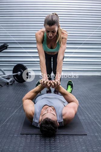 Muscular couple doing core exercises