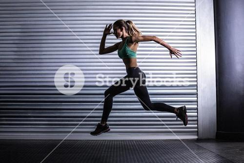 Muscular woman running in exercise room