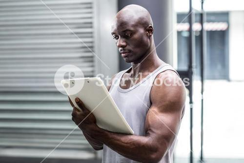Attentive muscular trainer writing on clipboard
