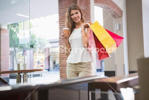 Portrait of smiling woman with shopping bags and coffee to go looking at camera