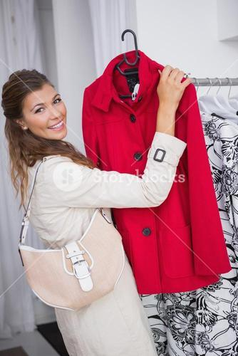 Portrait of smiling woman showing red coat and looking at camera