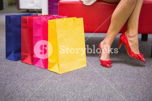 Woman sitting with legs crossed next to shopping bags