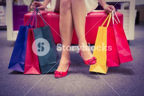 Woman sitting with legs crossed and holding shopping bags