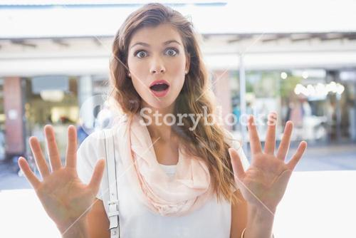 Portrait of astonished woman touching window with both hands