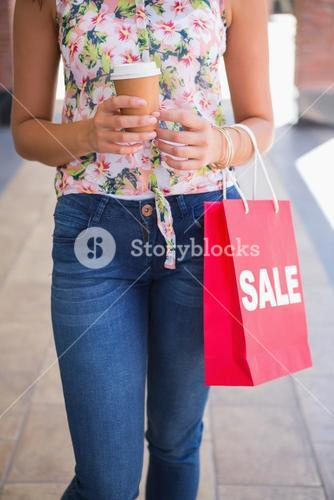 Woman walking with coffee to go and shopping bag
