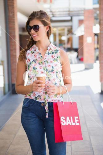 Smiling woman with sunglasses, coffee to go and shopping bag