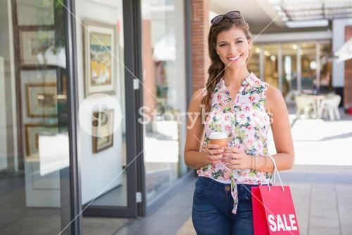 Portrait of smiling woman with sunglasses, coffee to go and shopping bag