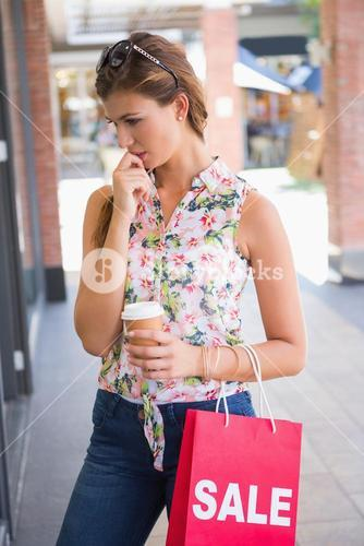 Focused woman with sunglasses, coffee to go and shopping bag