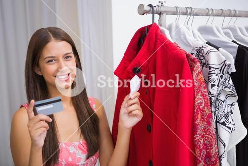 Portrait of smiling woman looking at red coat and holding credit card