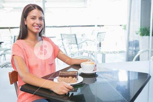 Young happy woman with cake and coffee