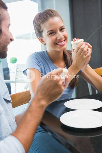 Young happy couple eating cake